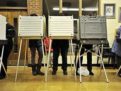 Legs of people behind 3 voting booths
