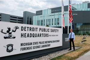 Reid Wilson standing outdoors in front of sign: Detroit Public Safety HQ