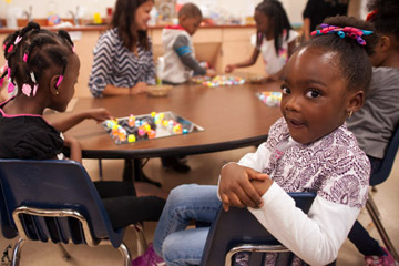 Young African American girl seated at table, smiling into camera. Teacher and other children at table in background.