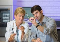 Female and male doctors seated next to each other looking at a sensor.