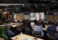 Groups of people seated at tables looking at screen with image of a woman talking.
