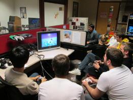 Bunch of guys sitting around playing video games.