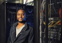 Photo of Prof. Mars wearing jean jacket standing next to server rack.