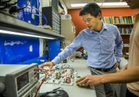 Photo of Prof. Kevin Fu and colleague at lab table surrounded by testing equipment.