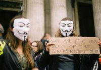 Two masked protesters holding a cardboard sign: We are the final boss of the internet.