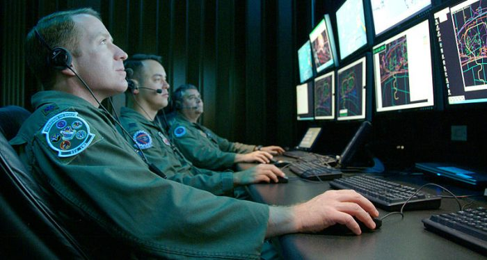 Three male army personnel sitting at computer screens.