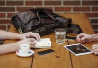 CU photo of wooden table with people's hands, mobile devices, coffee, water glass, and purse.