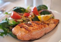 photo of grilled salmon and vegetables on a white dinner plate.