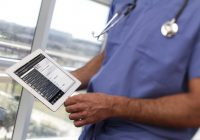 Doctor holding iPad showing medical record