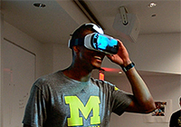 A man in a U-M T-shirt wears a virtual reality headset