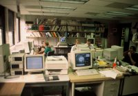 Office with computers and bookshelves, people sitting at desks, circa early 1990s.