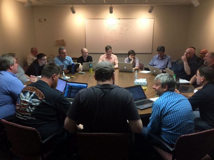 Team members of IIA, Network Operations, Network Security Operations, and Network Engineering, gather around a table to talk through potential attack scenarios
