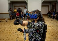 A woman demonstrates the HTC Vive virtual reality headset at the School of Information