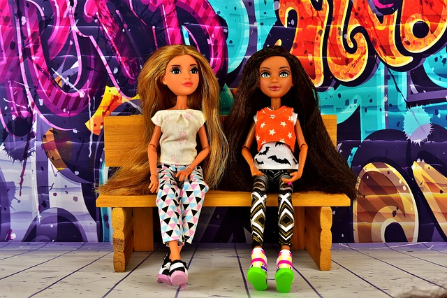 two dolls sitting on a bench