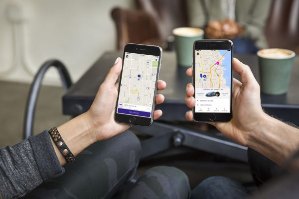 hands holding smartphones showing Lyft app