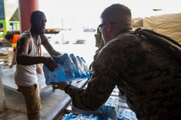 A U.S. Marine helps a civilian airport employee deliver water for distribution