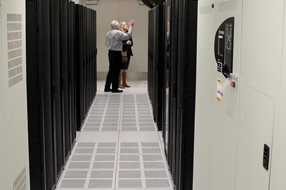two people looking at bank of servers