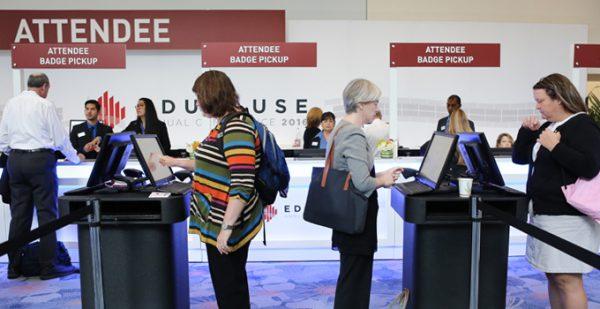 People standing at EDUCAUSE registration kiosks