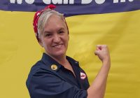 A woman impersonating Rosie the Riveter smiles and flexes her bicep