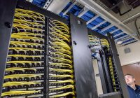 A rack of networked machines are pictured in a communications closet