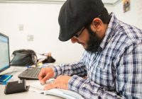 bearded man in cap sitting at computer