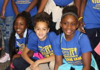 Three young African American girls smile and pose at Girls Are IT! STEAM JAM 2017
