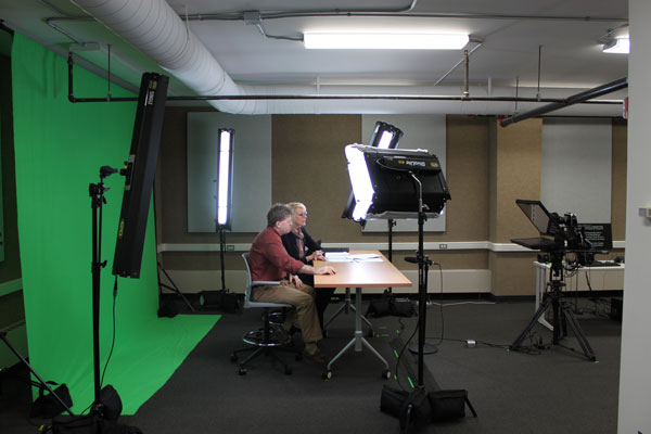 video studio with man and woman sitting at desk behind studio lights