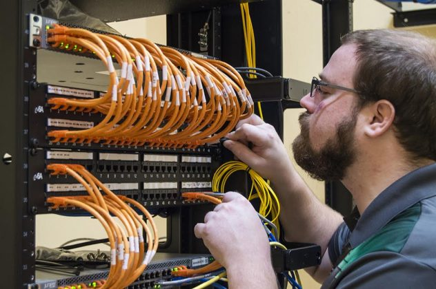 Bearded man with glasses working at router rack