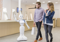 Human-like robot waves to a couple of shoppers