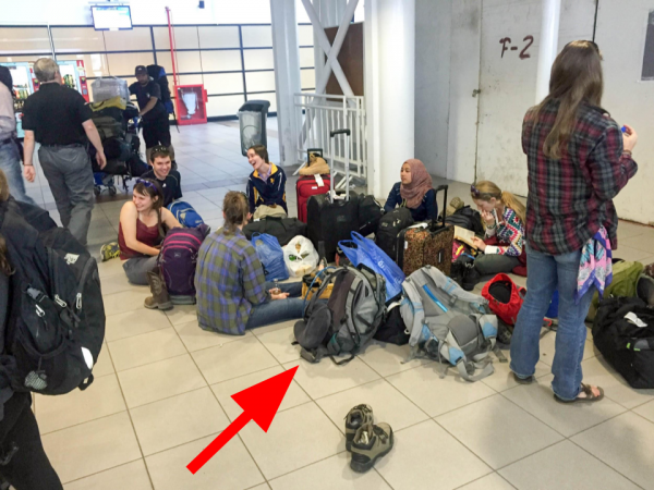 students sitting on floor of airport terminal surrounded by luggage.