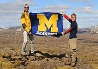 two students standing in an open field holding M Dearborn banner