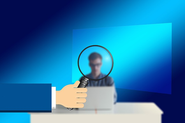 man at computer viewed through a magnifying glass