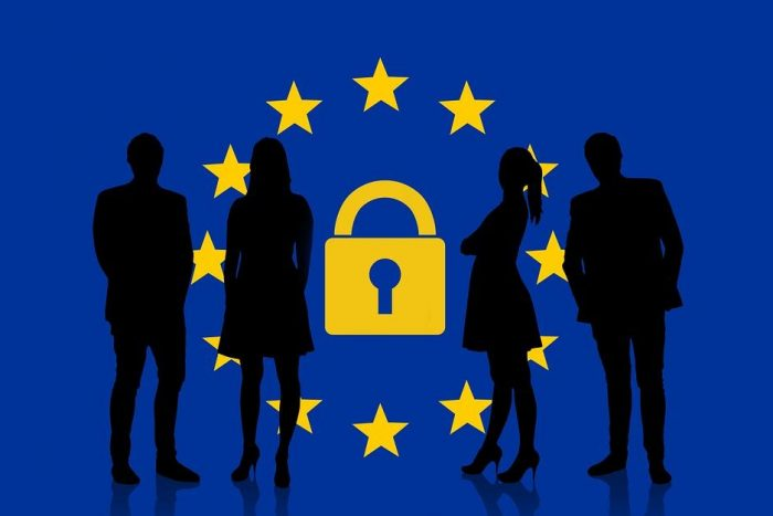 silhouette of people standing in front of EU flag with a lock in the middle