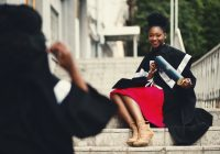 young african american woman wearing graduation robe, being photographed by another grad