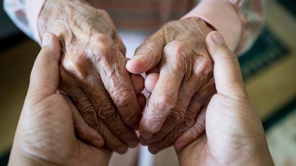 Holding hands with an elderly adult