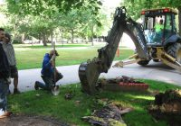 Man kneeling on ground as backhoe removes dirt.
