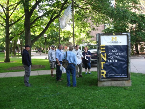 group of people standing around old Diag signage