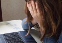 girl at computer holding her face in her hands