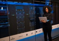 woman holding laptop standing next to server rack