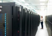 A woman standing in a data center amid rows of server racks