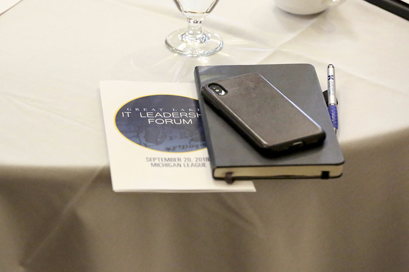 A picture of the Great Lakes IT Leadership Forum agenda, a notebook, a smart phone, and a pen laid out on a table.