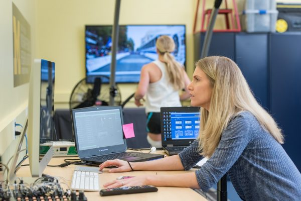 Blond woman working at computer with another woman in the background viewing a large video screen.