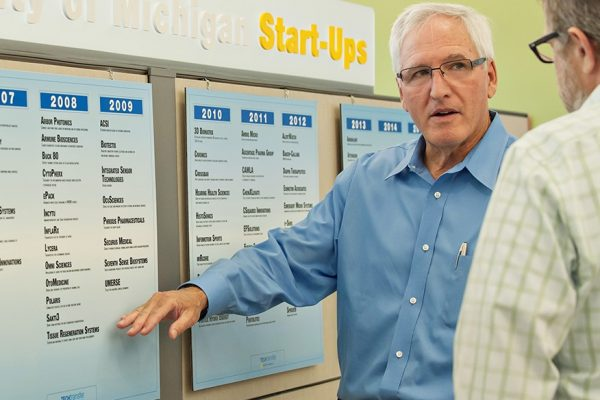 Man standing in front of posters showing lists of start ups by year.