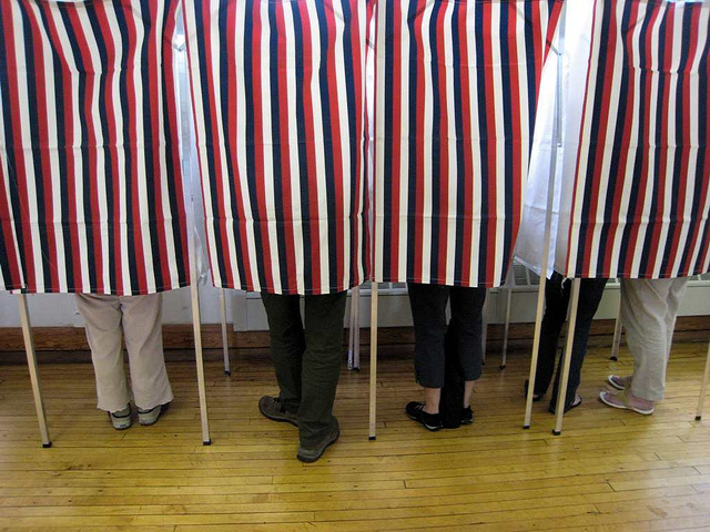 Curtained voting booths showing legs of people inside.