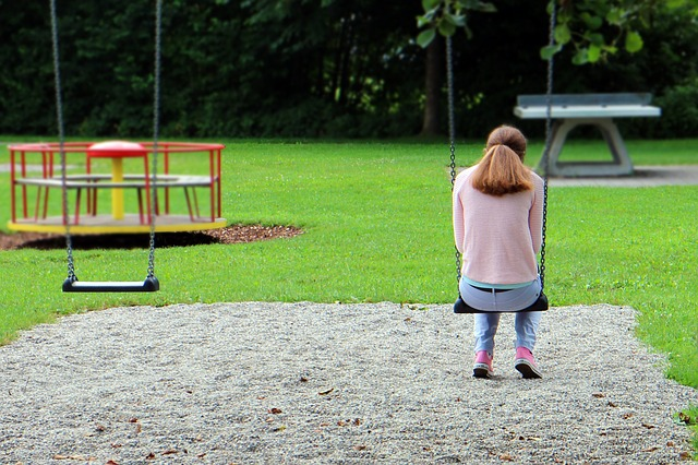 Sad woman on swing, back turned to viewer.