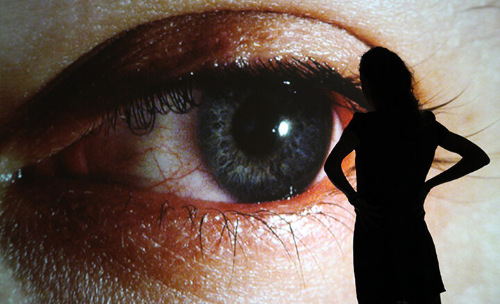 silhouette of a woman in front of a large photo of an eye