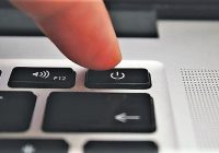 close up of finger pushing power button on laptop