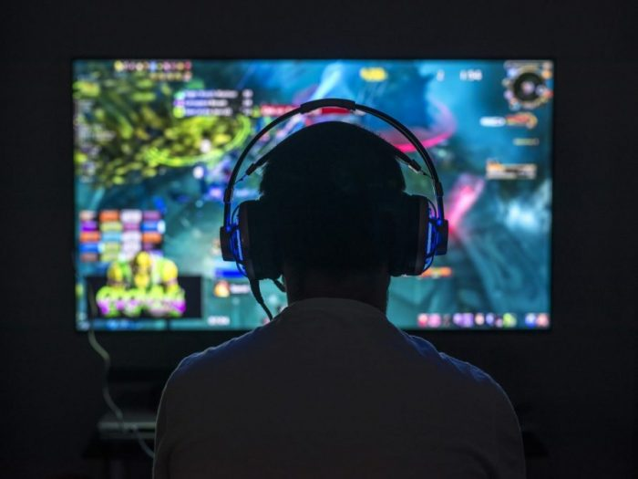 Gamer wearing headphones in front of computer screen.