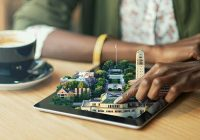 woman's hand hovering over miniature of central campus