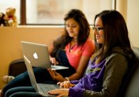two female students sitting on a sofa using laptops